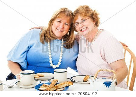 Two middle-aged best friends having a tea party together.  White background.