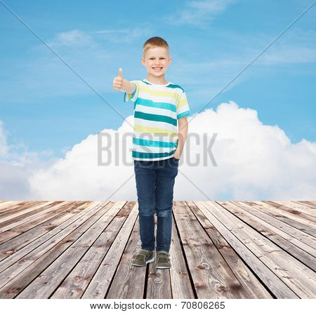 happiness, childhood, gesture and people concept - smiling little boy showing thumbs up over blue sky and wooden floor background
