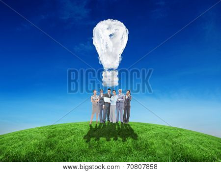 Business team looking at camera against cloud light bulb