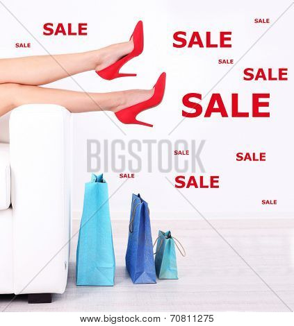 Concept of discount. Female legs in red shoes on sofa with shopping bags