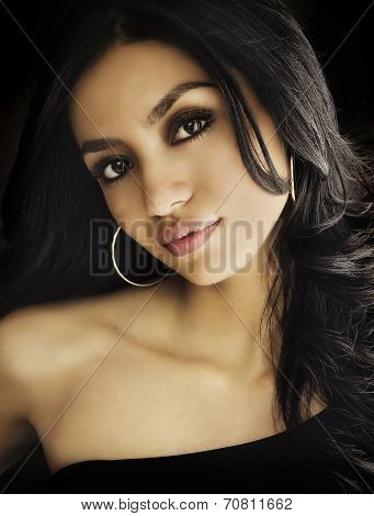 Beautiful exotic young woman's face dark sultry looks