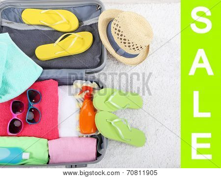 Concept of discount.  Suitcase with things  for summer travelling