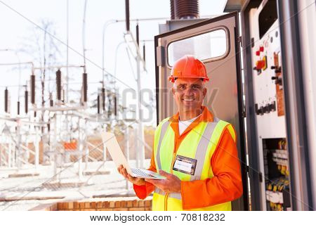 senior technician holding laptop in front of transformer at substation
