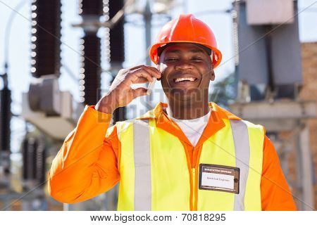 happy african electrician using cell phone in electric substation