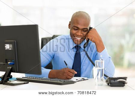 happy african businessman talking on landline phone and writing report