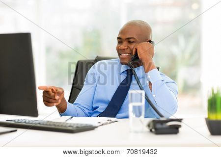 young african businessman talking on landline phone and pointing at computer screen