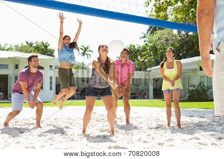 Group Of Friends Playing Volleyball In Garden