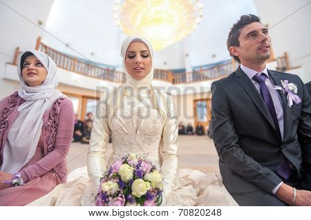 Islamic bride holding flowers sitting in a mosque on a wedding ceremony