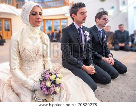 Bride and groom sitting in mosque at a wedding ceremony