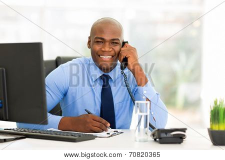 portrait of handsome male african office worker talking on phone