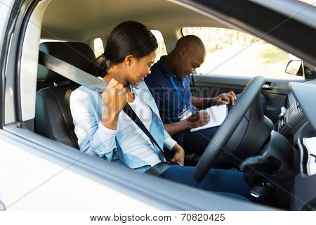 young african girl putting on seatbelt during a driving test