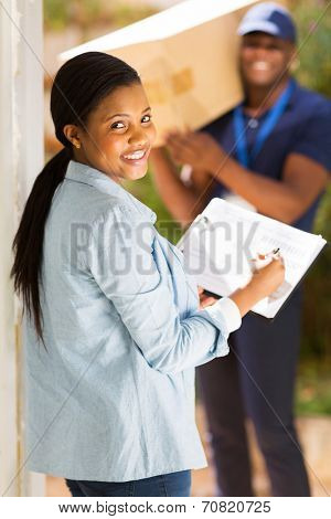pretty black woman signing document for receiving package