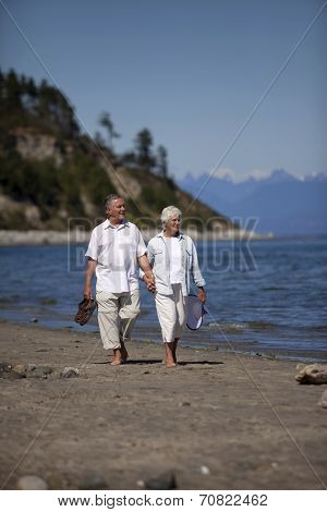 Vertical, outdoor photo of mature couple, holding hands, walking on ocean beach.