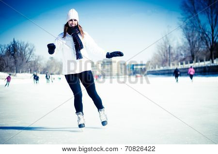 Attractive Young Woman Ice Skating During Winter - Blue Filter Applied