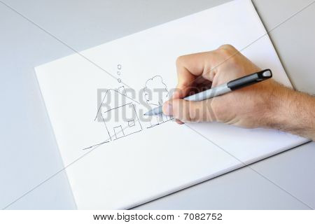 Male Hand Drawing House And Garden On White Paper