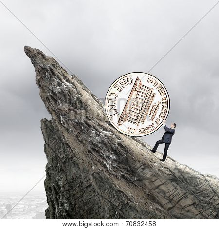 Businessman rolling cent coin up the hill