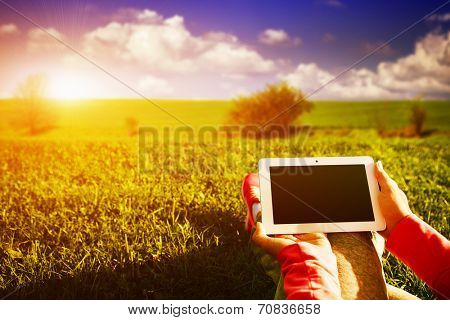 table pc in a hand for a girl on a background a green grass
