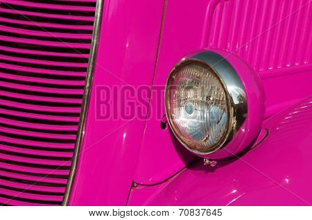 Closeup detail of the headlight of an antique car painted pink