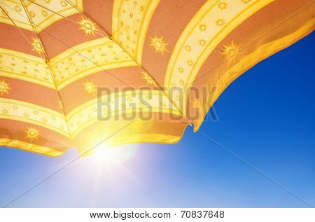 Detail of orange and red sunshade in the beach over a sunny blue sky