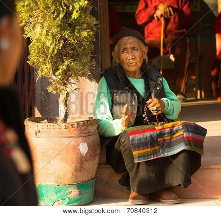KATHMANDU, NEPAL - DEC 11, 2013: Portrait of unidentified old woman near stupa Boudhanath. Stupa is one of the largest in the world, of 1979 is a UNESCO World Heritage Site.