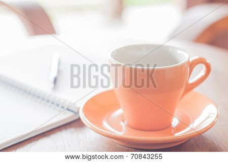 Orange Coffee Cup With Pen And Notebook
