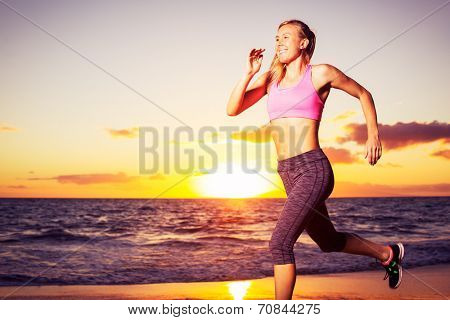 Athletic fitness woman running on the beach at sunset