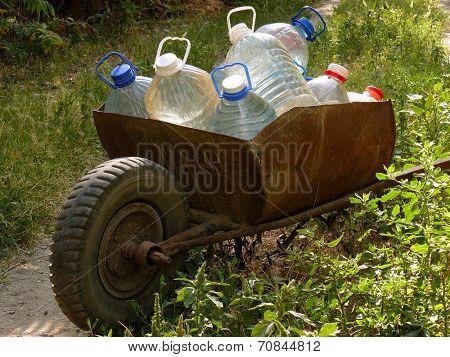 wheelbarrow full of plastic bottles with artesian water