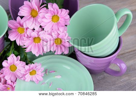 Bright dishes with flowers on wooden background