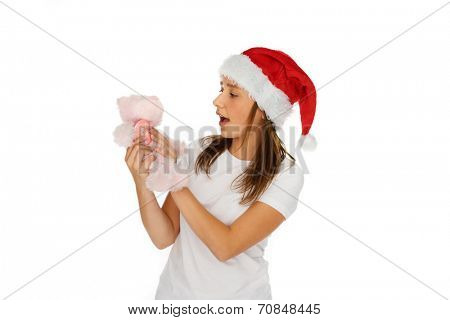 Young girl in red Santa Hat looking at a small plush pink teddy bear Christmas gift that she is holding in her hands with her mouth open in surprise, isolated on white