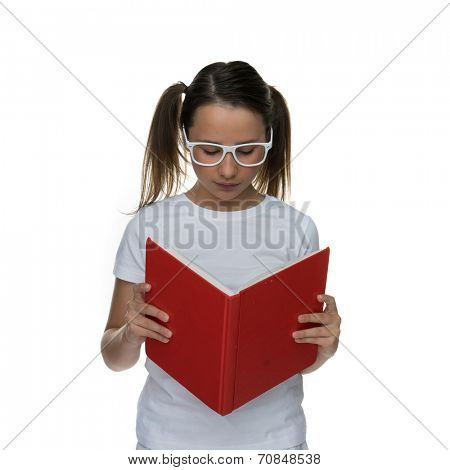 Young schoolgirl in modern white framed glasses standing reading a large read book with a serious expression, isolated on white