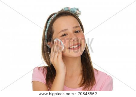 Beautiful young girl wearing a bow in her hair cleaning her face with a cotton pad smiling happily at the camera, on white
