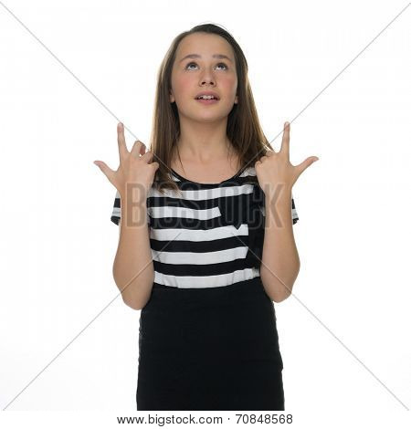 Pretty young girl standing pointing above her head with a happy smile towards blank white copyspace for your advertisement or text
