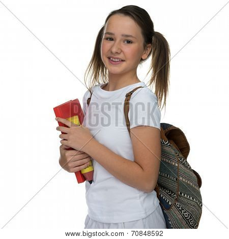 Smiling happy attractive young schoolgirl carrying a school book with her backpack over her shoulder standing looking at the camera, isolated on white