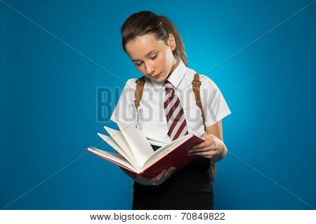Young schoolgirl standing reading from a class text book with her backpack on her shoulders, on a blue background