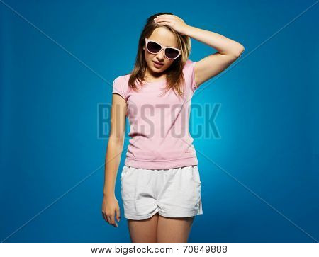Trendy young girl in summer shorts and sunglasses with a headache clutching her forehand with her hand and grimacing in pain, on blue