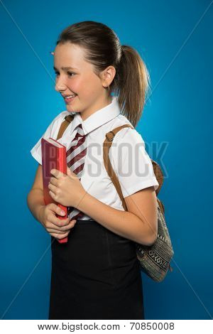 Happy young schoolgirl in her school uniform carrying a tex book with her backpack over her shoulders, side view on blue