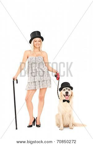 Full length portrait of a female magician holding a dog on a leash isolated on white background