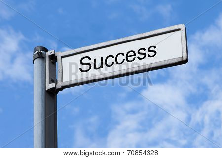 Signpost With Success Sign Against Sky