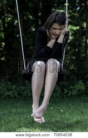 Worried Woman Sitting On Swing