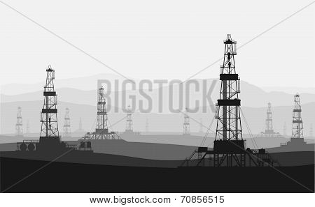 Oil rigs at large oilfield over mountain range.