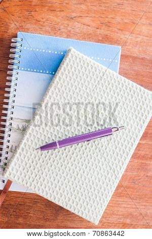 Pen And Two Of Notebooks On Wooden Table