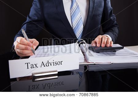 Accountant Calculating Financial Expenses At Desk