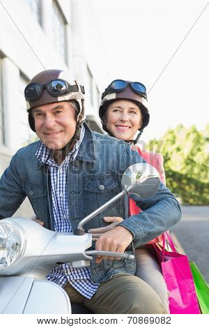Happy senior couple riding a moped on a sunny day