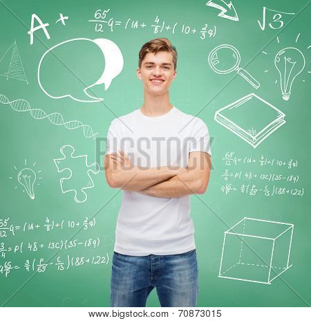 t-shirt design, education, school, advertising and people concept - smiling young man in blank white t-shirt over green board background with doodles