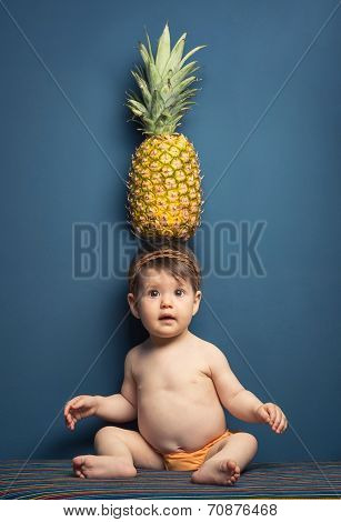 Happy baby girl holding a pineapple over her head