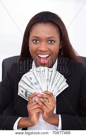 Businesswoman Holding Money Fan In Office