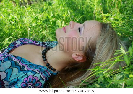 The young girl the blonde lays in a green grass in park