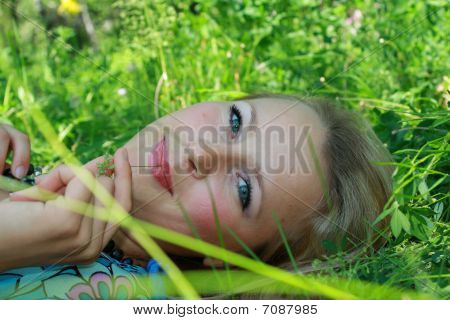 The Young Girl Lays In A Grass