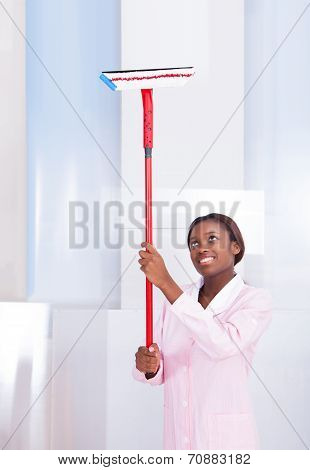 Housekeeper Cleaning Glass In Hotel