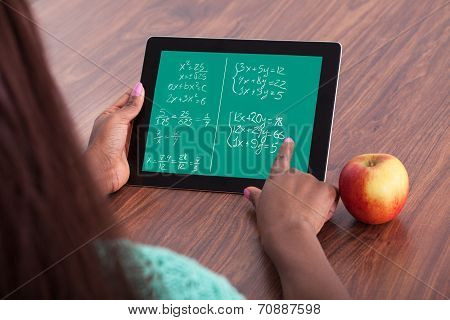 Student Solving Maths Problems On Digital Tablet